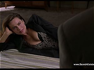 black-haired Lena Olin in undergarments displays off her small jugs
